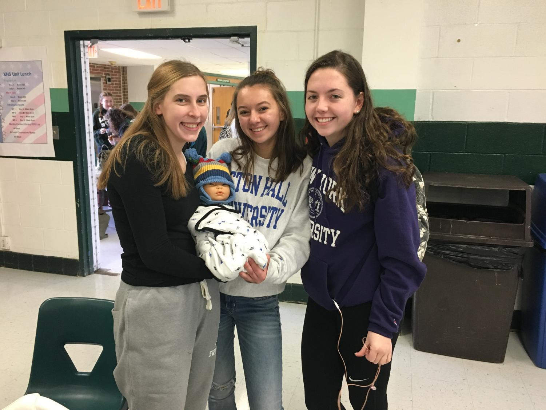 Seniors Emma Dougherty, Alicja Weglarz, and Danielle Donker with their baby.