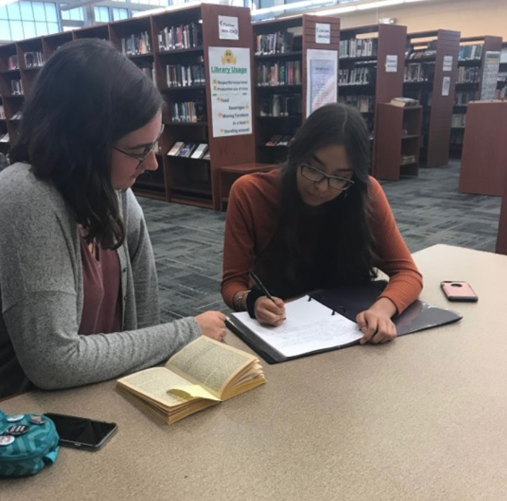 Senior Erin O'Mara helping Freshman Gabriella Cruz with an assignment.