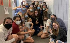 Morgan Festa (middle) and Carley Hall (right), along with their floor, celebrate Festa's 18th birthday with a chocolate cupcake while wearing the required masks.