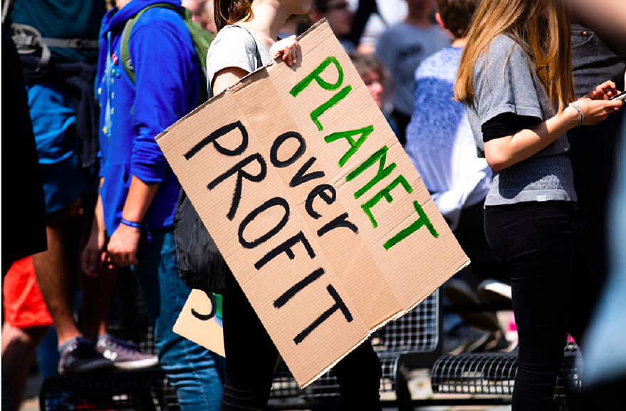 "Photo by Markus Spiske on Unsplash. Protestor walking by with a sign that states ""Planet over Profit."""
