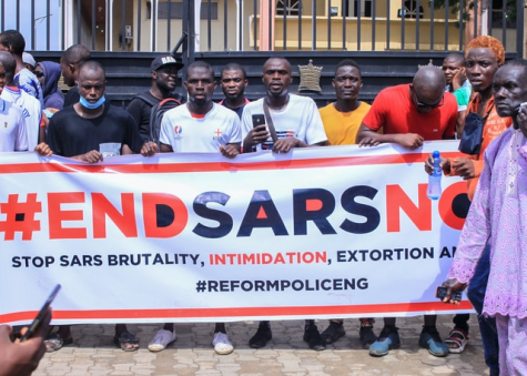 Photo by Tobi Oshinnaike on Unsplash. Nigerian Citizens holding up a #ENDSARSNOW Poster