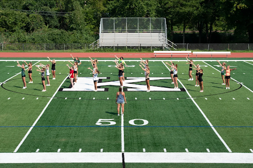 The cheerleaders working on jumps on the brand new turf field.